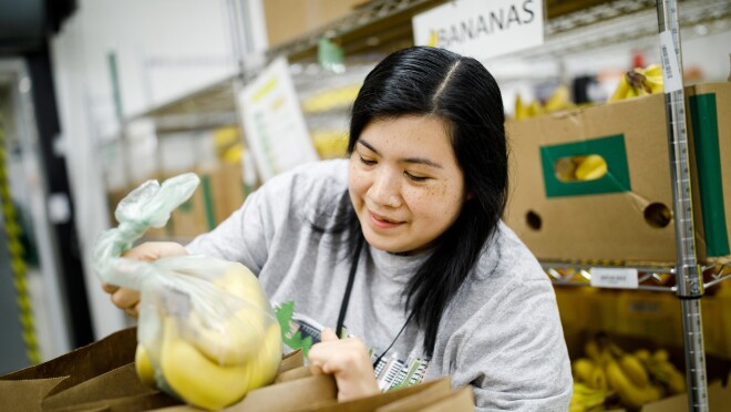 Prime Now associate Erika Lopez lifts a clear plastic bag containing bananas into a brown shopping bag.