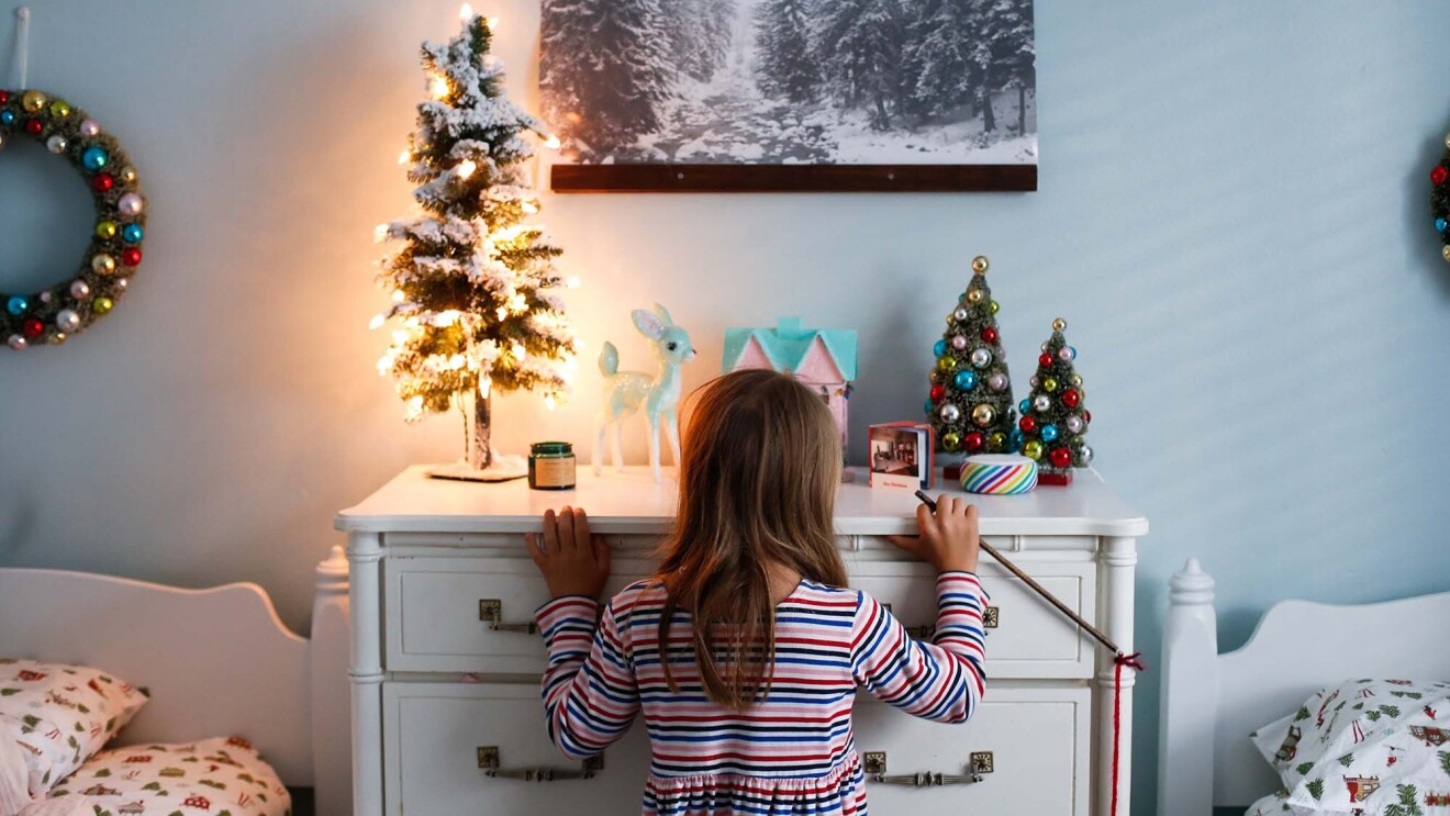 A young girl stands in front of a dresser, in front of an Alexa Echo device and small Christmas tree.
