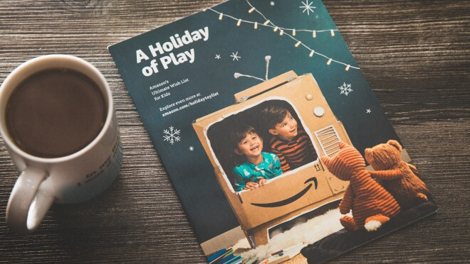 The 2018 Amazon holiday toy catalog, on a wooden tabletop, next to mug of cocoa.