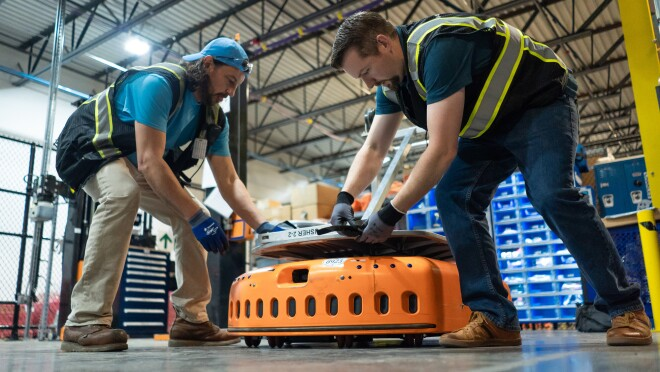 Two men in a warehouse space reach down to secure a silver-colored object to an orange, wheeled piece of machinery.