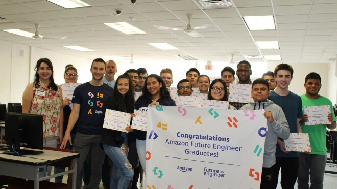 A group of students gathered in a classroom, standing behind an Amazon Future Engineer poster.