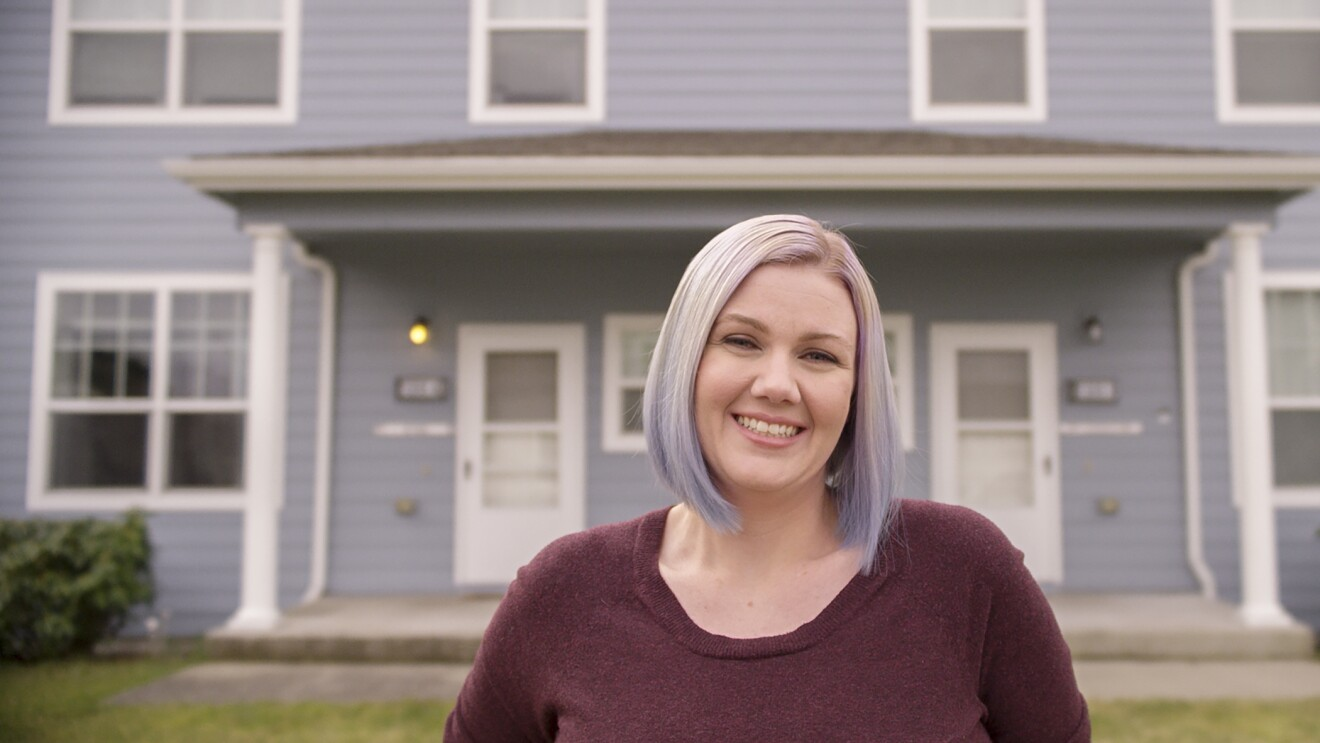 A woman stands in front of her home, smiling at the camera.