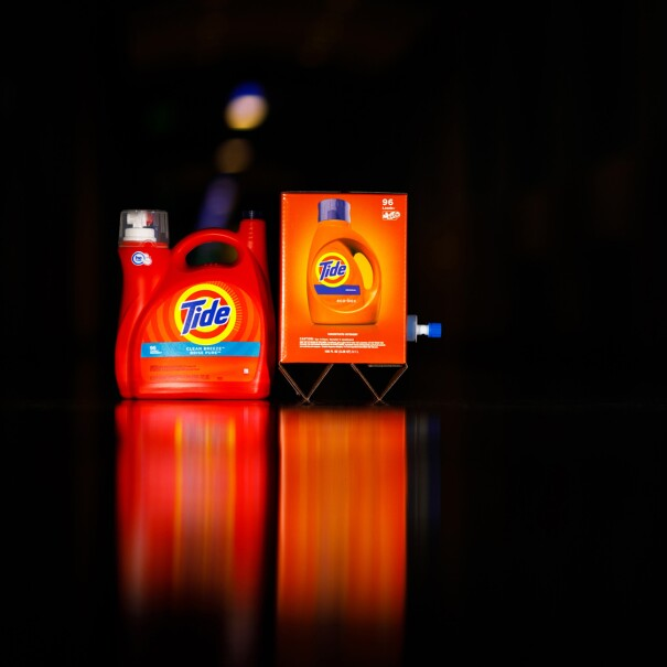 Two different types of packaging for Tide laundry detergent photographed against a black background. The package on the left is plastic. The package on the right is cardboard.