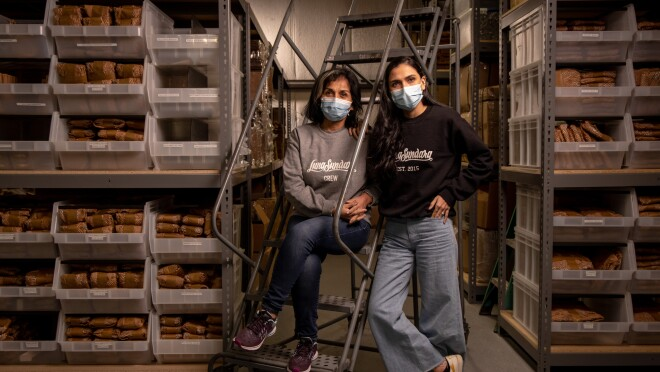 Two women in sweatshirts and jeans flanked by shelving in a warehouse space.