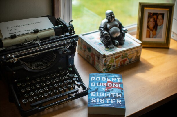 "Author Robert Dugoni's workspace within his home office, a refurbished typerwriter sits near a window. To it's left, a small box topped with a Buddha figurine, a copy of his book ""The Eighth Sister"" and a framed photograph."