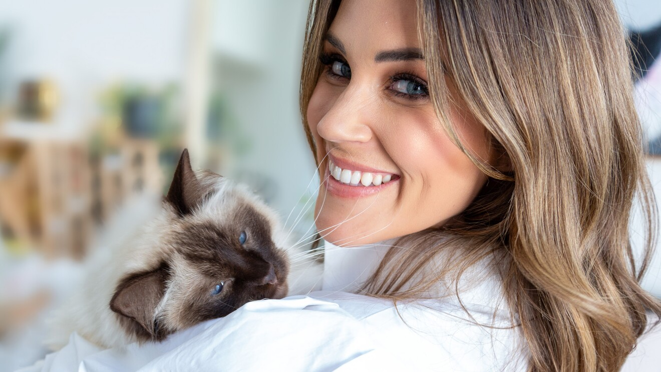 A television personality who is a woman holds her Siamese cat and smiles at the camera