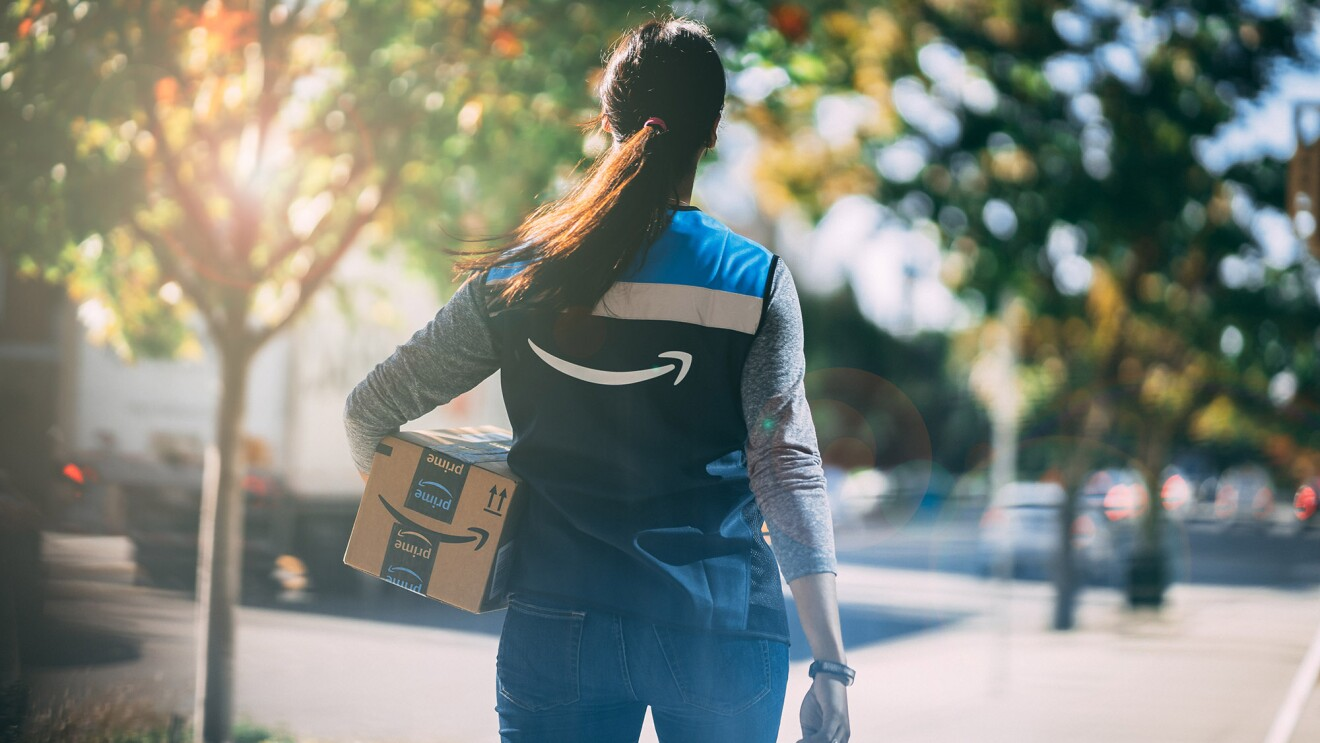 Amazon delivery driver walking toward a house