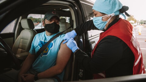 A man receives a COVID-19 vaccination while seated in his car at a drive-up vaccine clinic for Amazon Pharmacy employees.