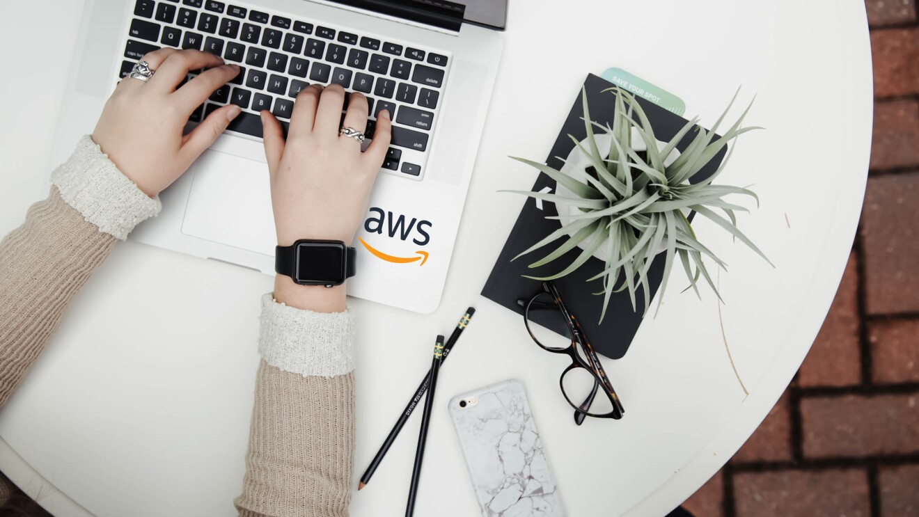 AWS logo seen in the laptop and a woman's hands seen using the laptop