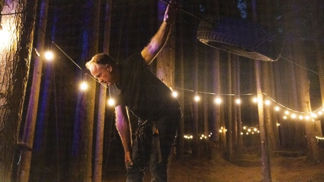 A man in a forest with strings of lights behind him.