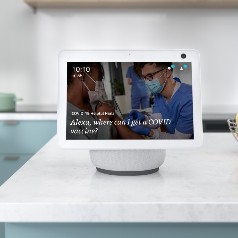"""An Alexa device sits atop a white kitchen countertop and the screen reads """"Alexa, where can I get a COVID-19 vaccine?"""" There is a wire basket filled with pears, limes, and apples next to the device. In the background there is a seafoam colored pot on the stove."""
