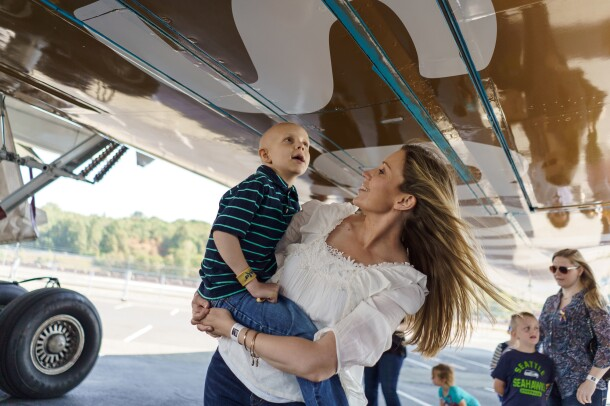 A young boy admires the bottom of a Prime Air aircraft, painted gold to support Childhood Cancer Awareness Month. Behind him, more children and their parents explore.