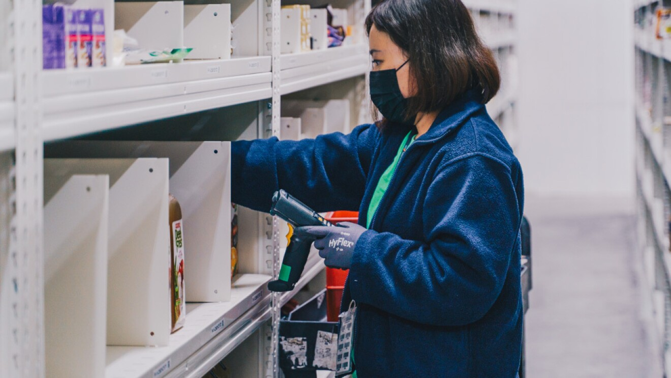 An employee scanning product codes within the chiller in the Amazon Fresh fulfillment centre