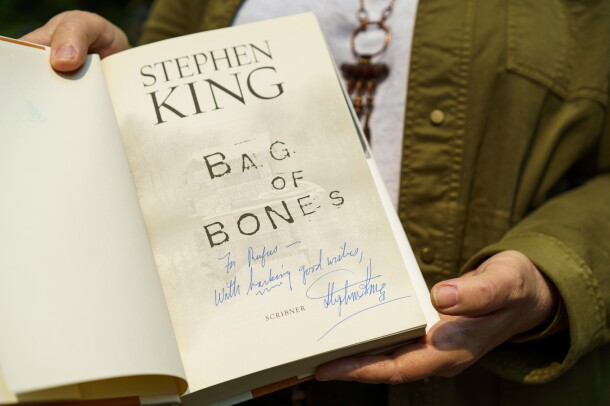 A man holds the book Bag of Bones by Stephen King. The inscription reads 'For Rufus, with barking good wishes.""