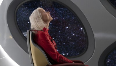 An image of Helen Mirren in a spaceship. She is wearing a red jumpsuit and looking at the ceiling above here. There is a window behind her with stars and space in the background.
