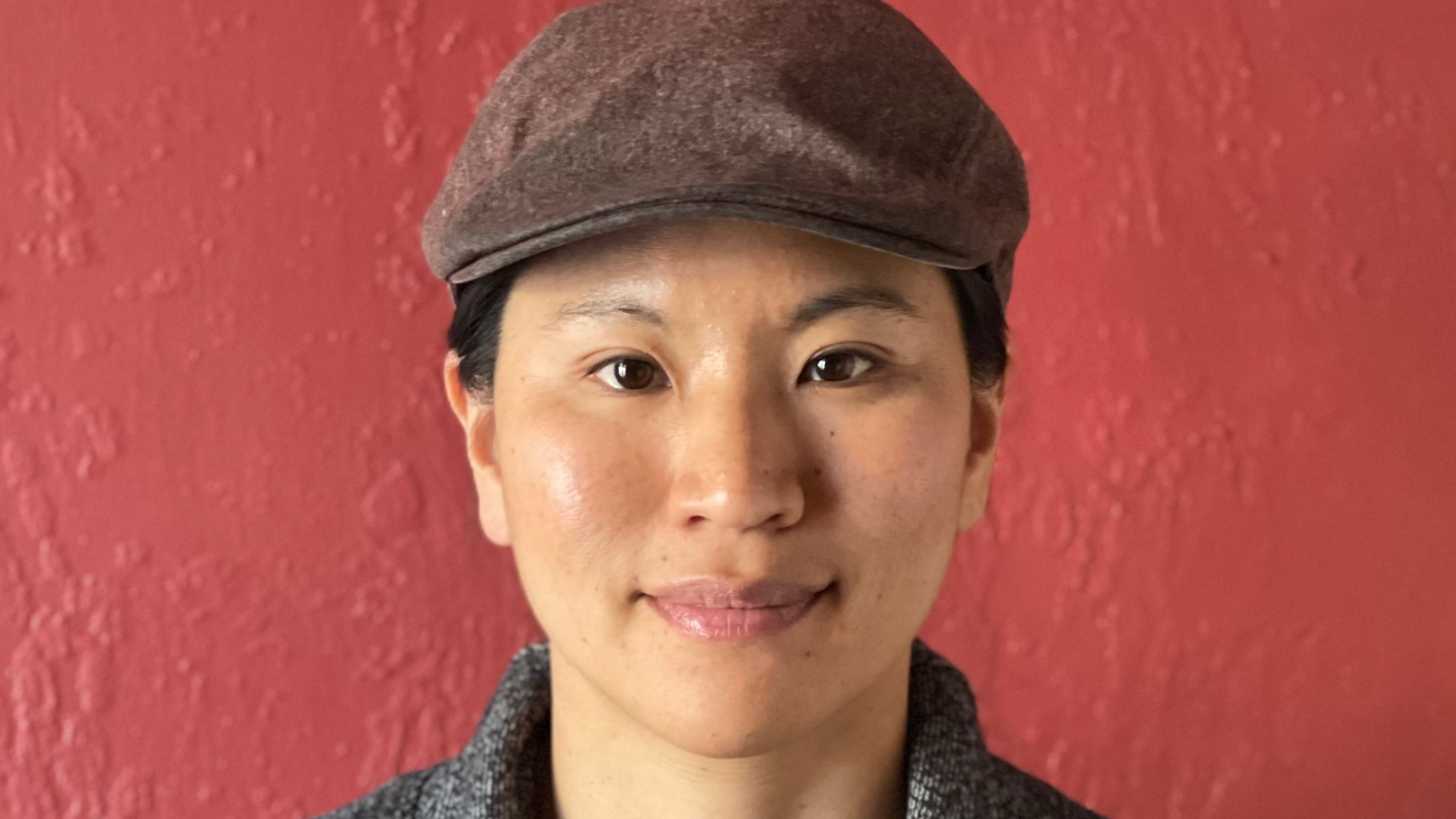 A woman wearing a newsboy cap, henley shirt, sweater, and necklace sits in front of a red wall.