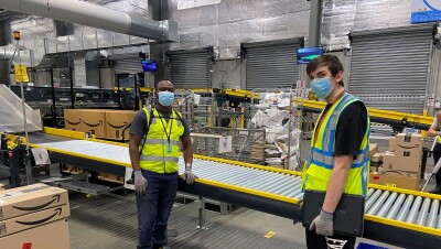 Two men stand in an Amazon fulfillment center, near a conveyor. They both wear a face mask, safety vest, and work gloves.