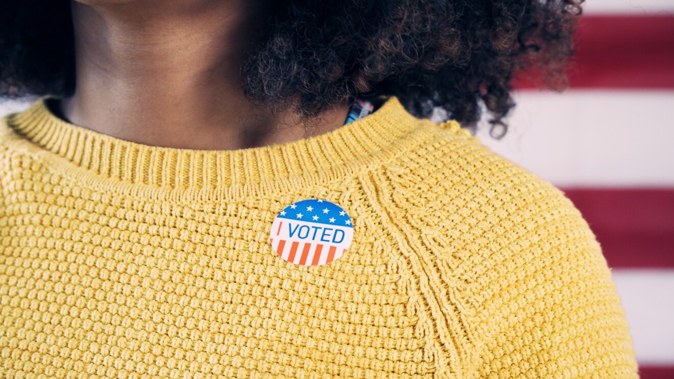 "A woman with brown skin and curly hair wears a yellow sweater. Upon that sweater, she wears a sticker that states, ""I VOTED"" with white stars on blue background, and red and white stripes."