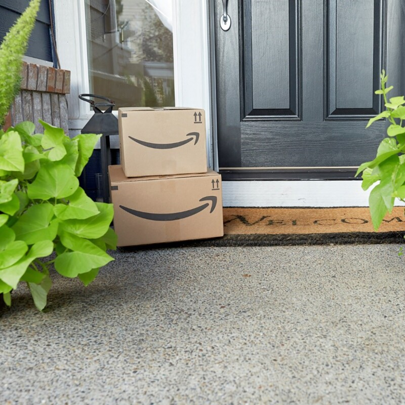 Two Amazon packages stacked on a door mat on a front step.