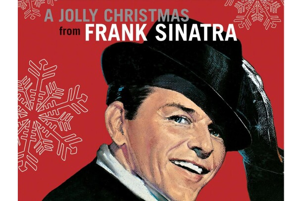 Frank Sinatra wears a suit and white button down, with a rimmed hat on his head, hair slicked, twinkle in his eye. His black gloved hand reaches up to tip his hat. He smiles toward the camera. The background is red, with large illustrated snowflakes falling around him.