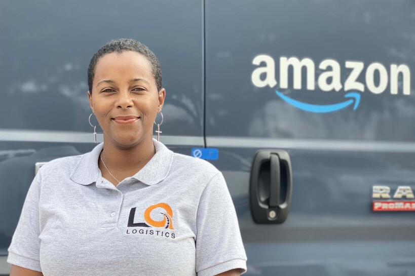 Amazon Delivery Service Partner Quanique Toston stands in front of an Amazon delivery van.
