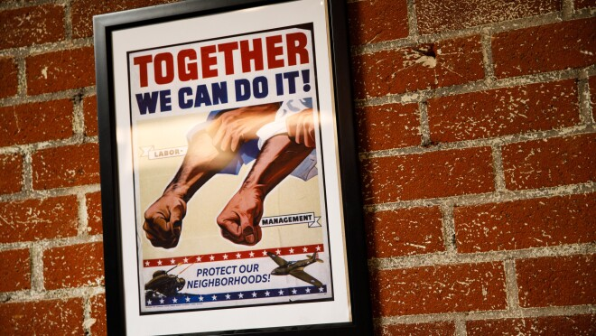 A poster on a wall at Ring headquarters showing clenched fists and rolled up sleeves. The slogan says 'Together We Can Do It! Protect Our Neighbors'.