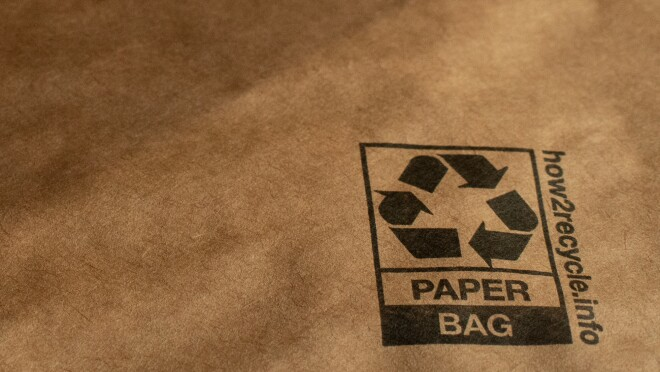 "Detail of a padded mailer showing a recycling symbol, the words ""paper bag,"" and a website: how2recycle.info"