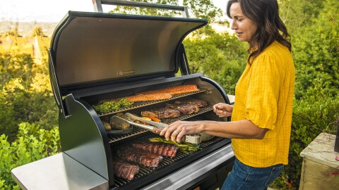 An image of a woman wearing a yellow shirt standing at a grill. The grill is full of meat and vegetables and she is using long, grilling tongs to flip the food. There is greenery in her backyard in the background.