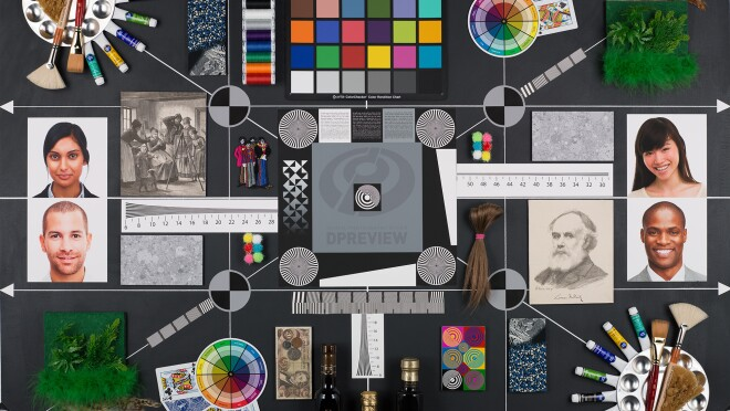 This dark gray rectangle has dozens of objects and images affixed to it. All of the items are used to test the performance of new cameras, lenses, and smartphones. There are four photos of people, two men and two women, with a range of different skin tones. There are various color swatches showing a rainbow of shades. There is old Austrian currency. There are artificial plants. There are also various detailed patterns, including Siemens stars.