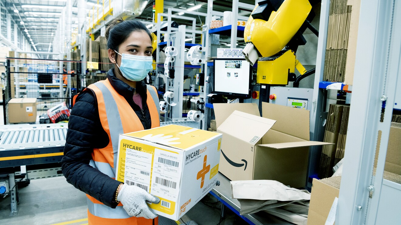 An Amazon employee at Coalville fulfillment center packs boxes with medical supplies to be sent to relevant government centers. She is wearing protective gloves and a face mask.