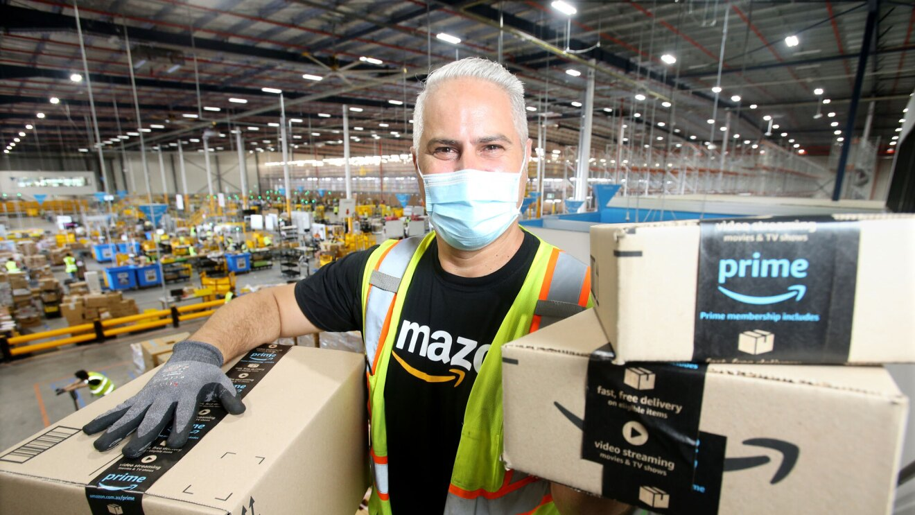 An Amazon employee in a fulfilment centre wears a mask and safety vest and is holding Prime packages up for the camera.