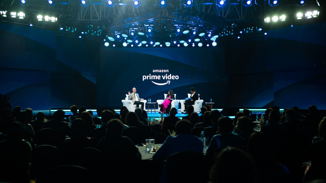Jeff Bezos sits on stage with Bollywood star Shah Rukh Khan and director Zoya Akhtar during Prime Video in India update and announcement.