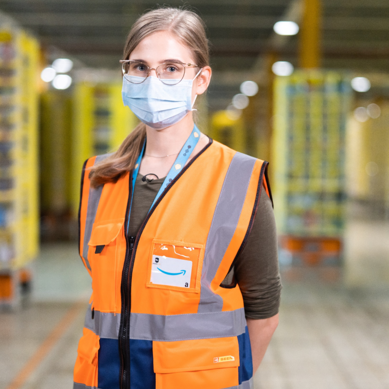 A woman wearing glasses, a face mask, and an orange safety vest stands in an Amazon fulfillment center.