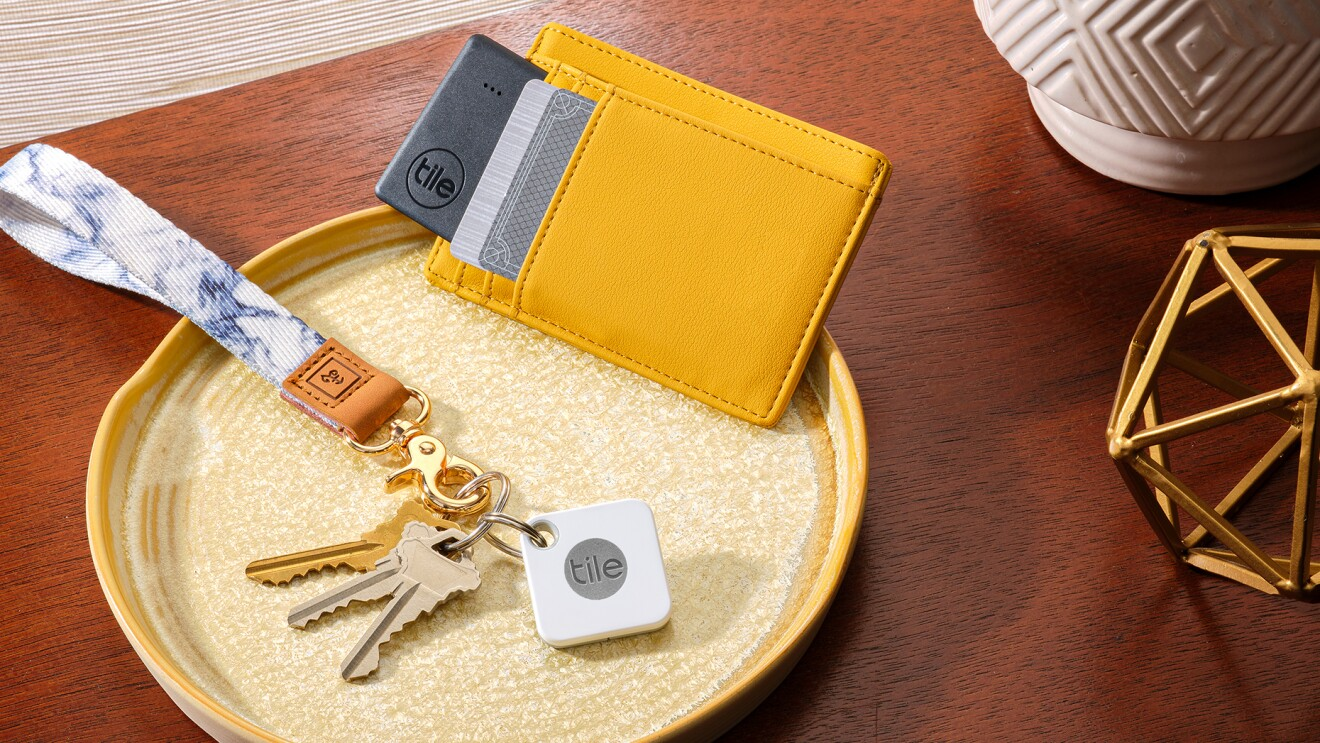 An image of a tray on a small table that holds keys with a hand-loop key ring and a Tile device. A wallet with credit cards in it sits next to the keys on the tray as well.