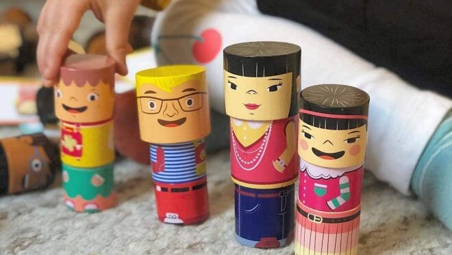 A child plays with four stacks of family builder toys.