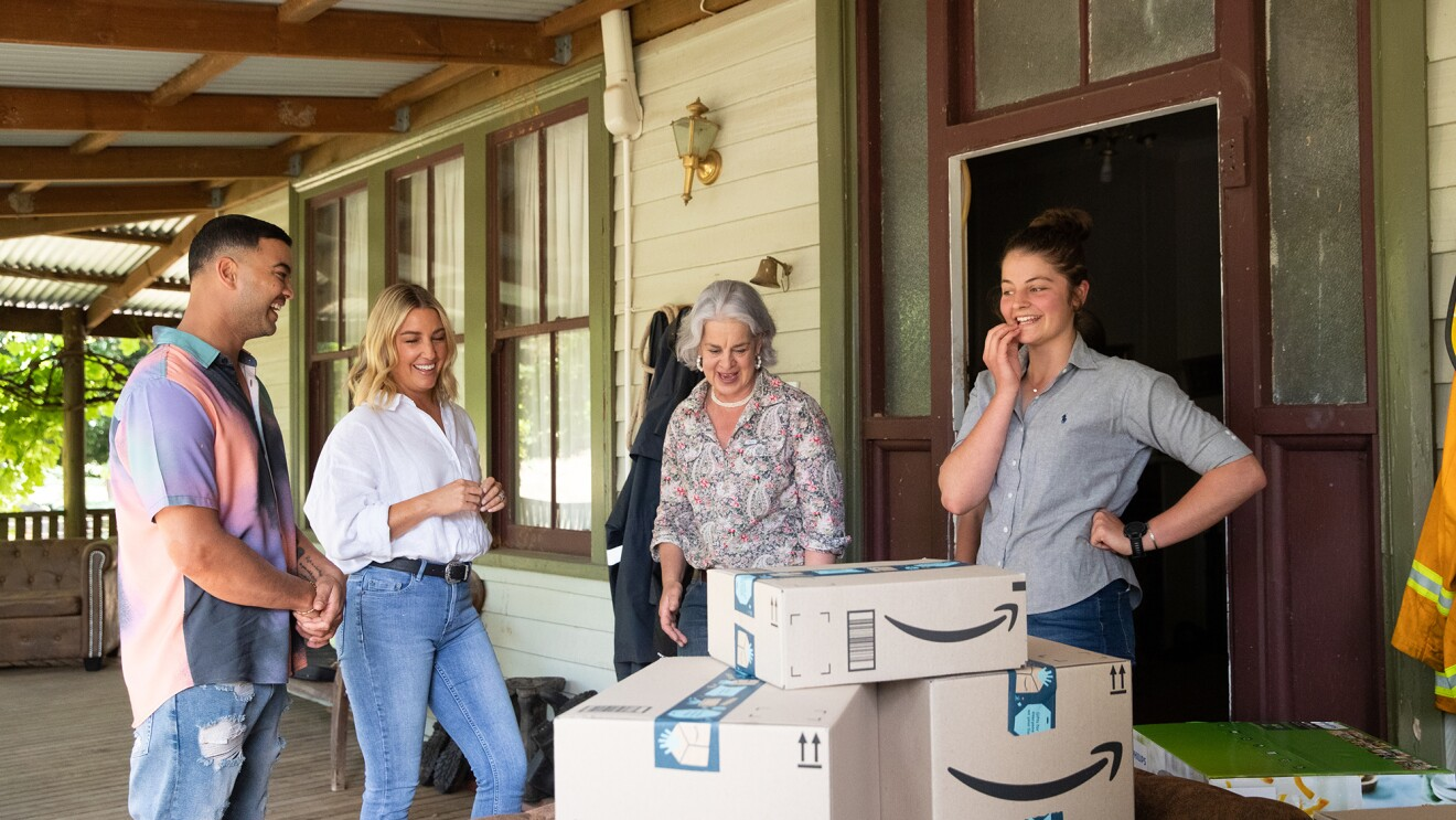 Three women and a man stand on the porch of a country home in Australia, beside a stack of Amazon boxes.