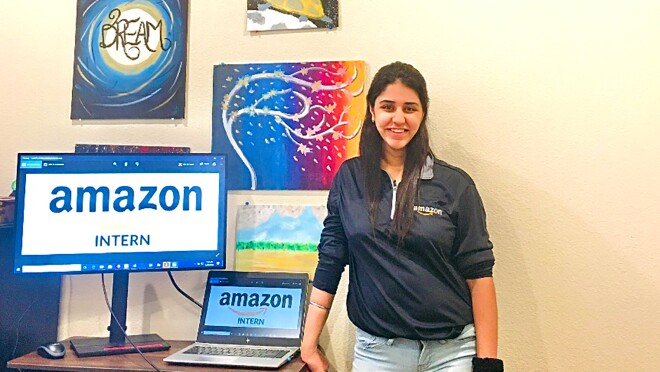 """A woman stands next to a desk with a laptop and monitor displaying the words """"Amazon intern."""""""