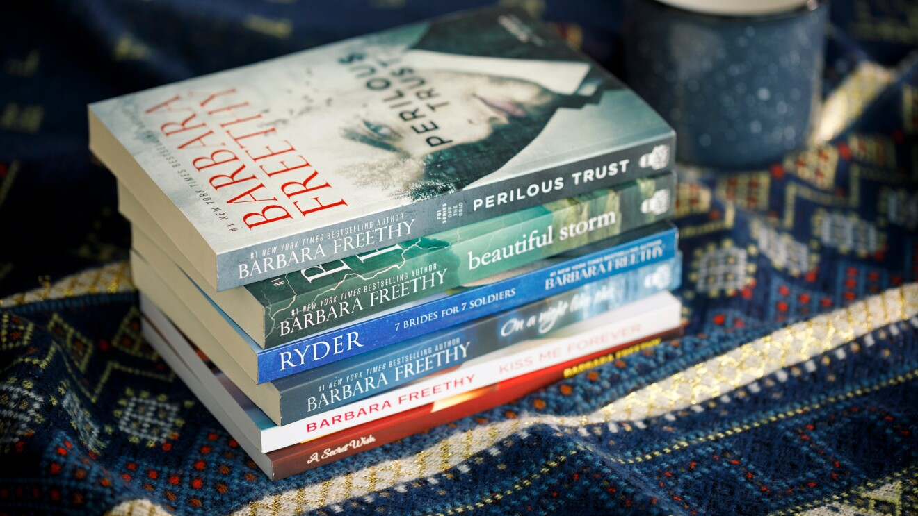 A stack of novels by Amazon author Barbara Freethy sits on a blue tablecloth. A blue coffee cup is in the background.