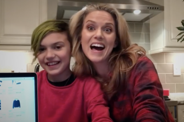 A woman and her child smile for a photo next to their laptop.