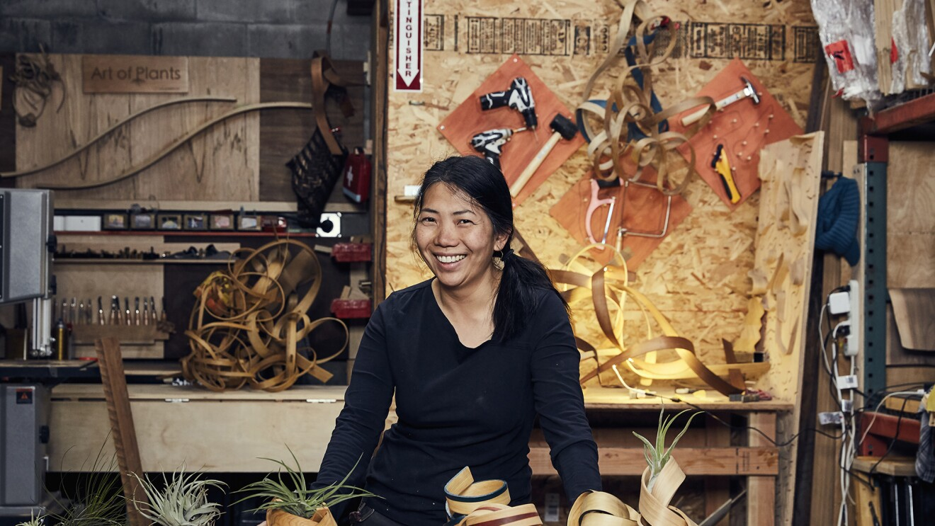 A woman stands behind a work table, smiling at the camera. In front of her are several handmade bentwood air plant containers, behind her sits more wood and tools.