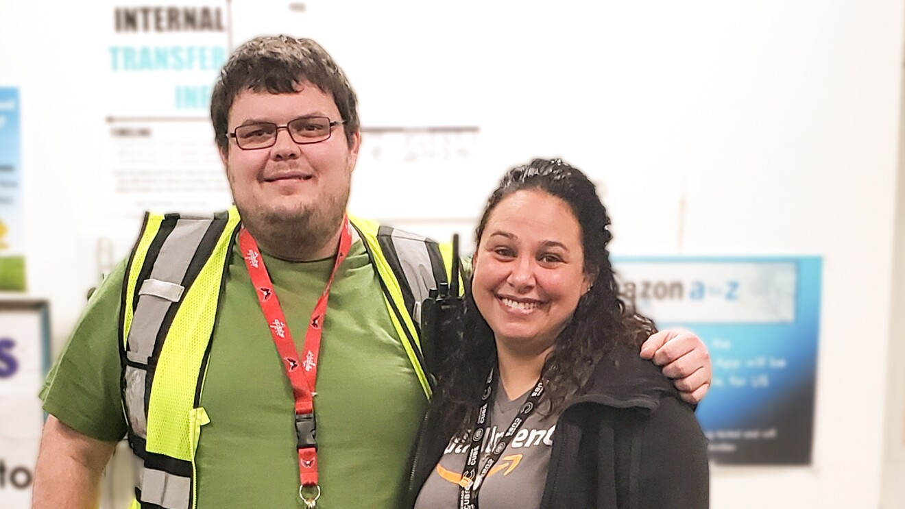 A woman and a man pose together for a photograph. The man wears a green T-shirt and a yellow safety vest. The woman wears a black fleece jacket and a gray T-shirt with the Amazon smile logo.