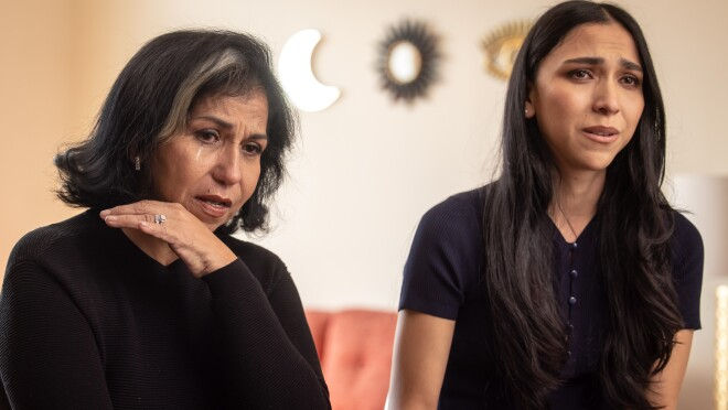 Two women sit side-by-side with emotional looks on their faces.