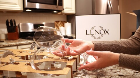 A person opens an improved Lenox wine glass package in their kitchen.