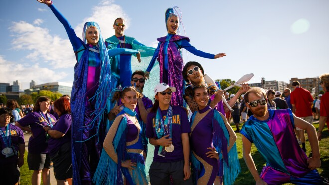 A Special Olympics USA Games athlete posts with event performers at the closing ceremony. The female athlete is wearing medals from the Special Olympics, while the performers include three stilt walkers (the two females are wearing elaborate headpieces), a juggler, and others in apparel (with lots of glitter, fringe and cutouts) that suggests a circus-themed show.