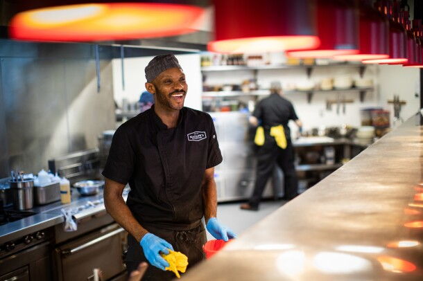 A cook smiles at customers from behind the line at Maslow's, by FareStart, in Seattle, WA.