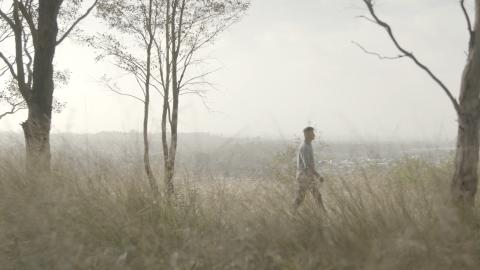 A man walks through the bush, the sky is hazy from the bush fires.