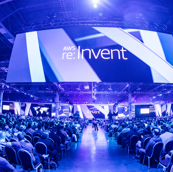 AWS re:Invent conference, view shows hundreds of individuals sitting in chairs at a conference. A huge screen hangs above them, the space is awash in blue light.