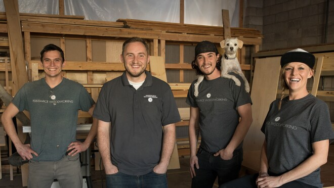 Three males and a female stand in front of a wall of wood. One of the men has a dog perched on his shoulders. These four individuals are siblings who run a small business named Pereida-Rice Woodworking, which sells on Amazon.