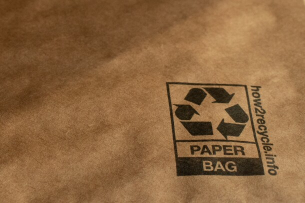 """Detail of a padded mailer showing a recycling symbol, the words """"paper bag,"""" and a website: how2recycle.info"""