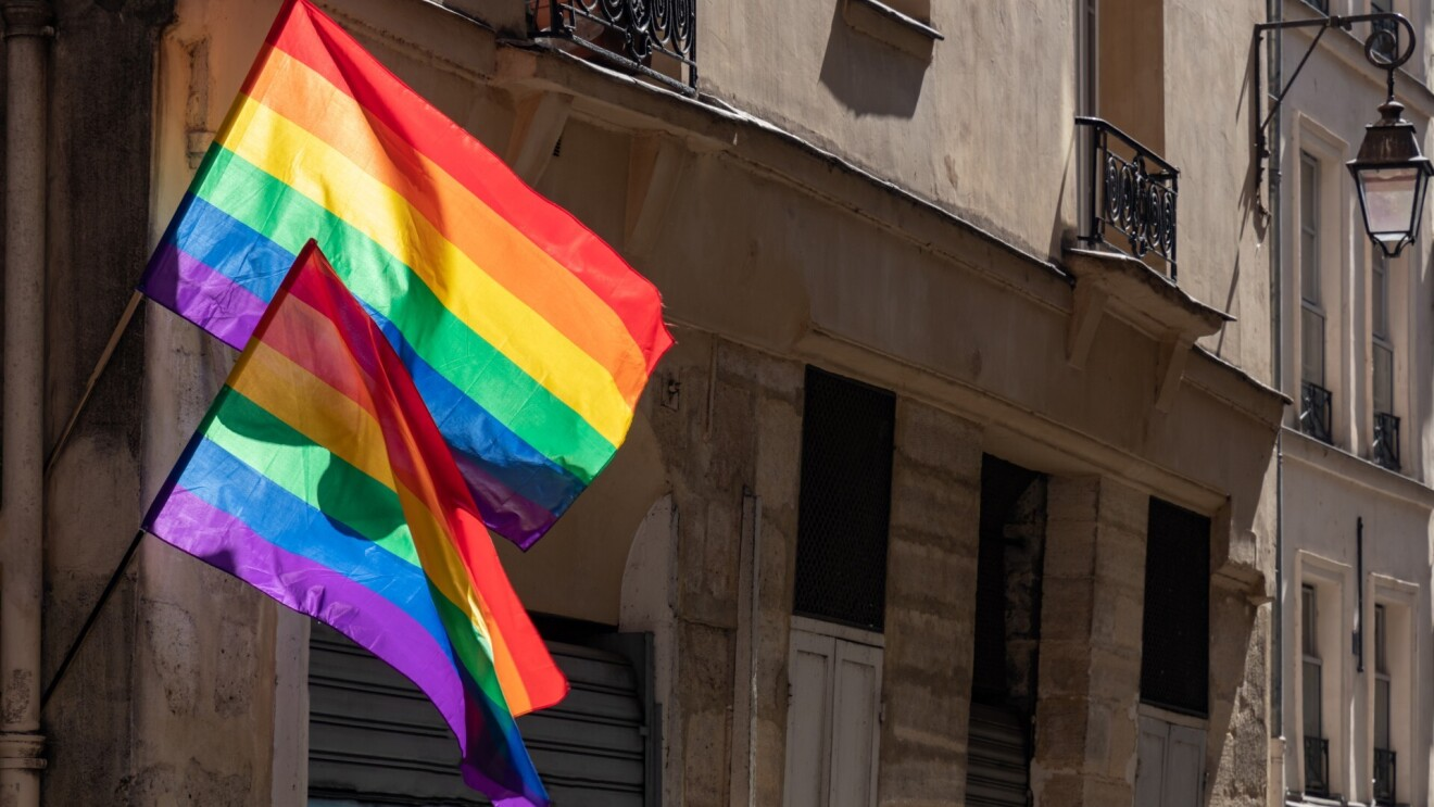 Two LGBTQ flags blow in the wind while attached to the side of an old historical building.